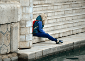 Teen girl sitting against a brick wall, looking away from the camera wearing a backpack. EMDR therapy for children in Scotch Plains, NJ can help your child feel more in control. Begin EMDR for kids in Scotch Plainst, NJ with virtual EMDR therapy in online therapy in New Jersey.