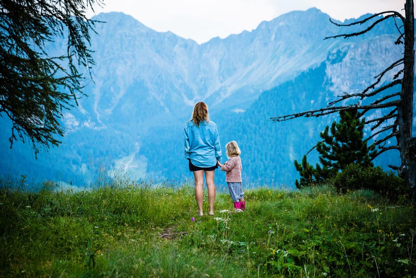 Mom and child standing among a mountain range