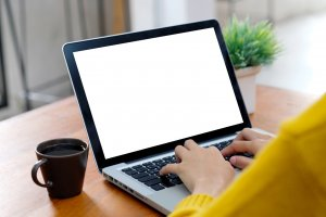 Woman typing on a laptop with a cup of coffee. Online Therapy in New Jersey is available for COVID 19 anxiety and stress to help with telehealth in New Jersey