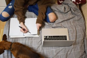 Teenager sitting on bed working with a dog. She or he could use online therapy in New Jersey to help with his anxiety and other issues. Online counseling in New Jersey or telehealth can help!