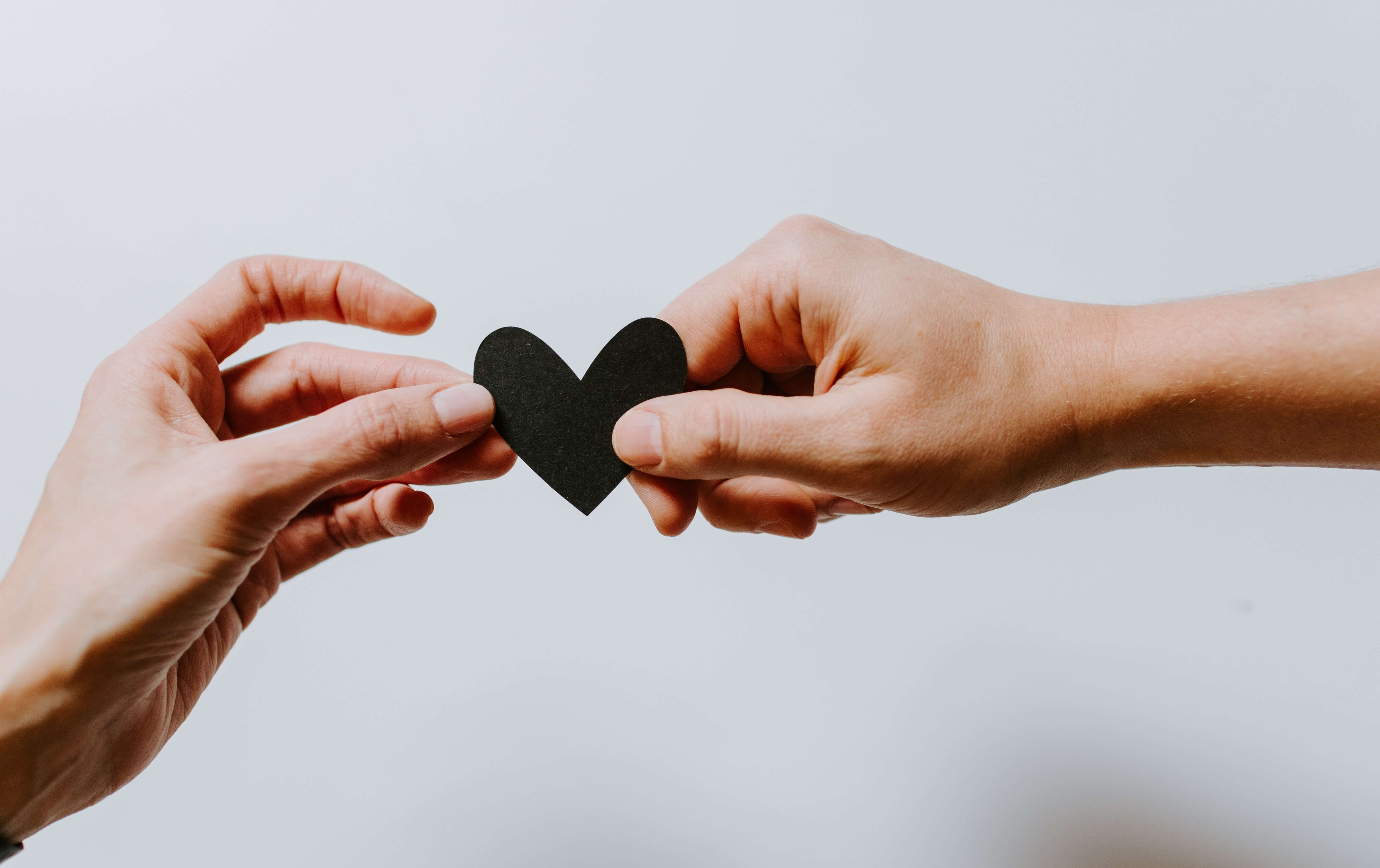 Two different hands hold either side of a black paper heart in front of a blank backdrop. Brave Minds Psychological Services offers couples counseling, marriage counseling, and more! Contact us today for support!
