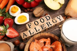 Allergy food as almonds, milk, cheese, strawberry, seeds, eggs, peanuts and crustaceans or shrimps with wooden letter food allergy. If you're wondering can food allergies cause panic attacks, you can get therapy for food allergies and anxiety attacks in New Jersey at Brave Minds Psychological Services.