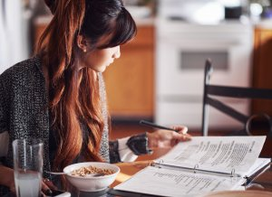 College student sits inside at the breakfast table. She looks over her notes while eating a bowl of cereal. They will have to use their laptop or tablet in order to make their classes. Brave Minds Psychological Services offers online therapy for college students in New Jersey. We also offer therapy for teens, and child therapy online in new jersey. Contact us today!