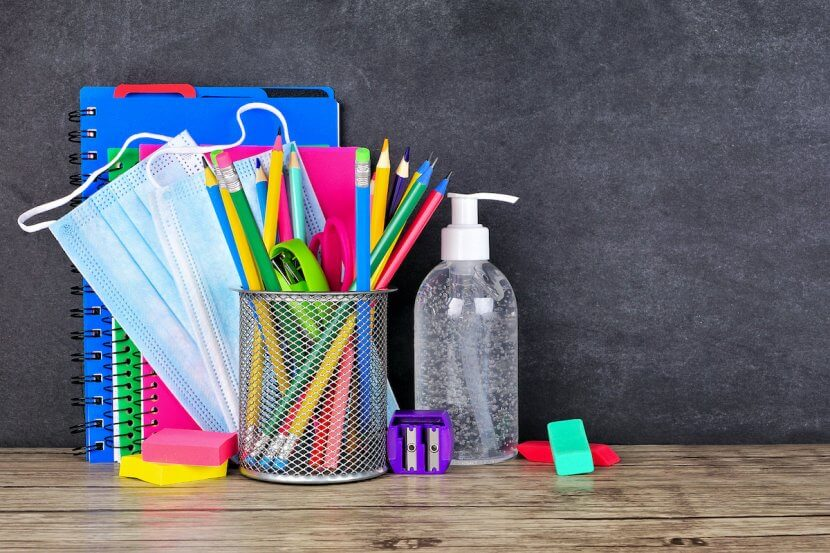School supplies and COVID 19 prevention items on a desk against a chalkboard background. Back to school during pandemic concept for virtual learning during COVID. You can get anxiety treatment in Westfield, NJ and Anxiety treatment in Cranford, NJ with Brave Minds in Scotch Plains, NJ