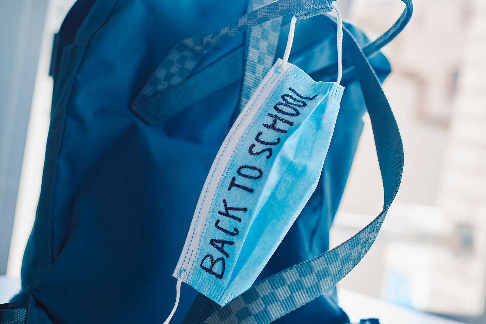 closeup of a green bookbag and a blue surgical mask with the text back to school written in it, depicting the need to prevent the infection at school in the covid-19 pandemic situation for virtual learning during COVID. You can get anxiety treatment in Westfield, NJ and Anxiety treatment in Cranford, NJ with Brave Minds in Scotch Plains, NJ
