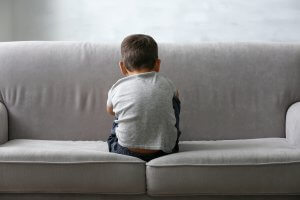 Little boy sitting with back to the camera, worried and scared. Child anxiety therapy in Scotch Plains, NJ can help with scary thoughts.