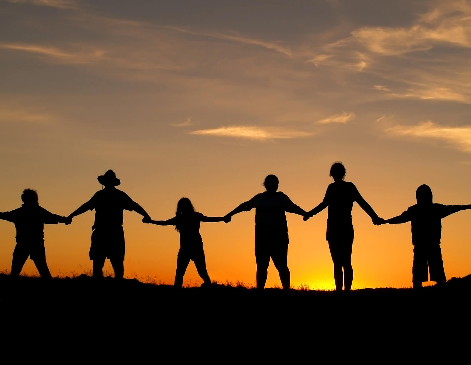 Unity and strength of a family holding hands in the sunset. Symbolizing the love languages for children and teens with anxiety for child therapy and teen therapy in Scotch Plains, NJ. You can get help with parent coaching and therapy for children with anxiety here and via online therapy in New Jersey