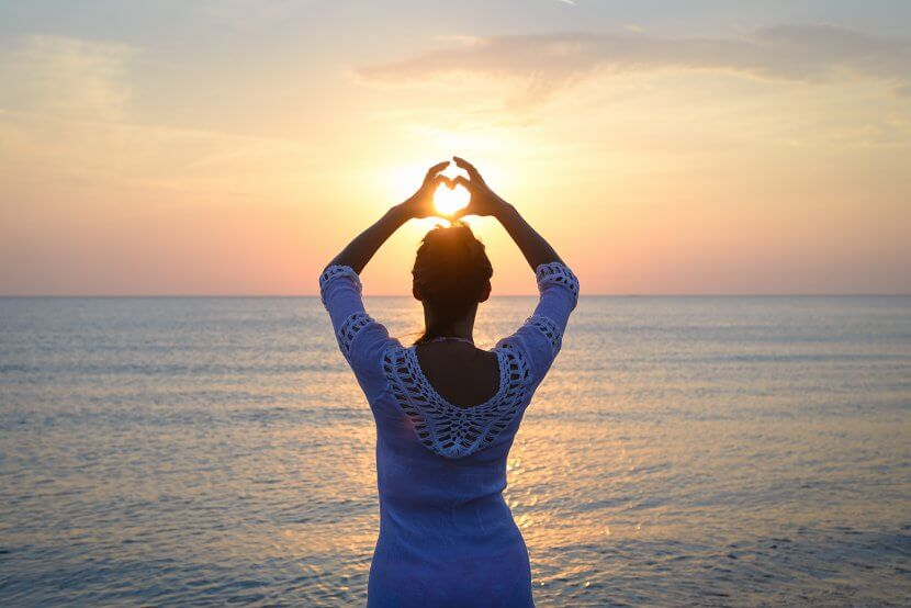 Woman Makes Heart With Hands On Beach. Symbolizing the love languages for children and teens with anxiety for child therapy and teen therapy in Scotch Plains, NJ. You can get help with parent coaching and therapy for children with anxiety here and via online therapy in New Jersey