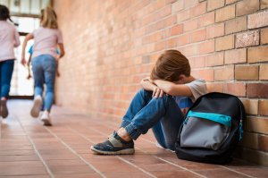 Little boy sitting against a brick wall with his backpack and arms on his legs with head in his arms. School anxiety makes his scary thoughts worse. He needs help from a child psychologist in Scotch Plains, NJ or in online therapy for children in New Jersey.