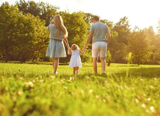 Happy family walking on the grass in the summer are doing well working with a child therapist for parent coaching for the love languages for children and teens with anxiety for child therapy and teen therapy in Scotch Plains, NJ. You can get help with parent coaching and therapy for children with anxiety here and via online therapy in New Jersey