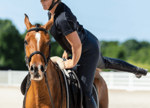 A rider mounts her horse with an uncomfortable look on her face as her leg sweeps around the saddle of the horse. This expression could represent the anxiety that comes from horseback injuries. We offer trauma therapy in Scotch plains, NJ to support you through events such as this. Contact a trauma therapist for support today.
