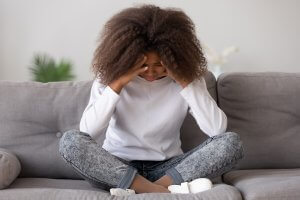 teen girl sits with her head in her hands on the floor after experiencing trauma and PTSD. She gets emdr for teens in Scotch Planes, NJ with an EMDR therapist