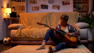 teen sitting on the floor of a bedroom playing guitar. he gets EMDR for teens with a teen therapist in Scotch Planes, NJ