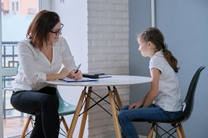 A therapist writes on her clipboard as she listens to the child across the table. This could represent a child therapist in Scotch Plains, NJ meeting with a client. Contact us to learn more about child therapy for anxiety and other services!