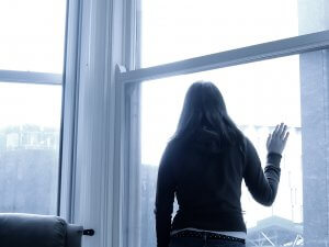 A monochromatic image of a woman in black looking out a window. This could represent the cold pain of trauma from the past. We offer EMDR therapy in Scotch Plains, NJ. Contact an EMDR therapist to learn about the benefits of EMDR for children.