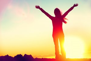woman at sunset stands with arms raised above her head in celebration. This could symbolize the feelings of freedom experienced after overcoming trauma. We offer EMDR therapy in Scotch Plains, NJ, EMDR for children, and more. Contact an EMDR therapist for support today.