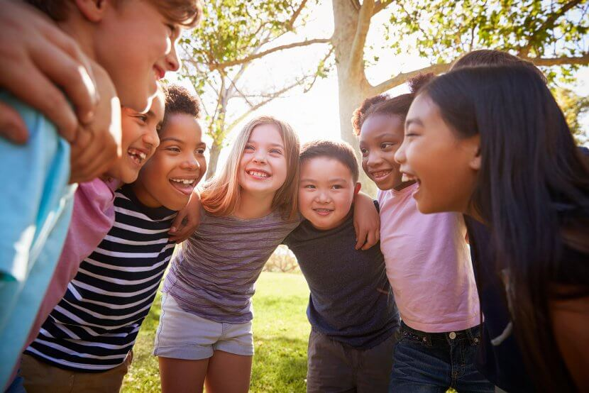 A group of kids huddle in a circle as they smile at one another. Contact a child therapist in Scotch Plains, NJ for support with child therapy for anxiety, EMDR therapy for children, and more!