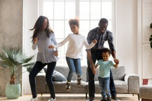 A happy family smile as they dance with one another in the living room. This could represent the joy a child therapist in Scotch Plains, NJ can help your family cultivate. Learn about child therapy for anxiety, EMDR therapy for children and other services.