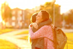 """A teen smiles as she hugs her friend on a sunny evening. This happiness could represent how counseling for teens in Scotch Plains, NJ can benefit relationships. Learn more about online therapy for teens by searching """"teenage anxiety therapist near me."""""""