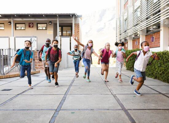 Diverse school age children wear masks while leaving a New Jersey School. Get counseling for childhood anxiety counseling in Scotch Planes, NJ at Brave Minds Psychological Services