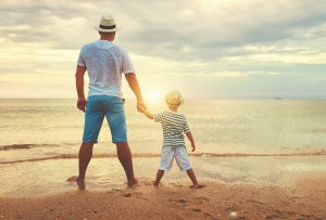 A father holds their child's hand as they watch the setting sun. This could represent the calm that anxiety counseling in Scotch Plains, NJ can help you and your child achieve. Contact a child therapist to learn more about child therapy for anxiety, anxiety treatment, and other services.