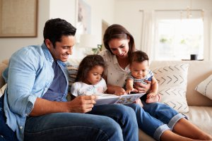 """A family smiles together as they read a book. This could represent the peace that anxiety counseling in Scotch Plains, NJ can provide with child therapy for anxiety. Contact us to learn more about anxiety treatment, or search """"teenage anxiety therapist near me"""" today."""