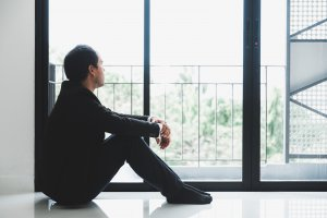 An Asian man sits on the floor as he looks outside. He appears lost in thought. Therapy for perfectionism in Scotch Plains, NJ can help you with perfectionism and overthinking. Contact a perfectionism therapist for support with anxiety counseling in Scotch Plains, NJ.