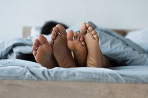 A close up of a couple's feet hanging out from under the covers. Parenting counseling in Scotch Plains, NJ can offer support with parenting help and sexual violence prevention in Scotch Plains, NJ! 07076