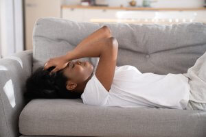A woman lays on a sofa with hands resting against her forehead. Sexual violence prevention in Scotch Plains, NJ can help prevent aganist rape culture. Learn how online therapy for sexual assault in New Jersey can help you today! 07076